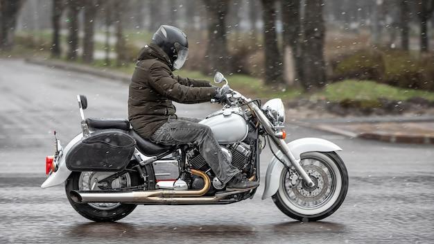 Un motociclista in un casco su una motocicletta da strada corre lungo la strada.
