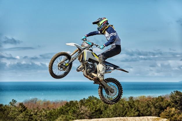 Il motociclista fa un salto estremo contro il cielo