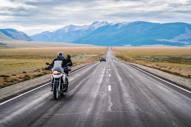 Motociclista con la mano alzata in segno di saluto a cavallo lungo l'autostrada chuysky russia montagna altai