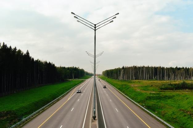 Vista dell'autostrada dal ponte. ampia autostrada in estate con lanterne.