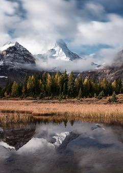 Monti assiniboine con la riflessione della foresta di autunno sul lago magog al parco provinciale