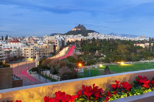 Il monte lycabettus che sovrasta i tetti della città vecchia durante l'ora blu serale ad atene, grecia
