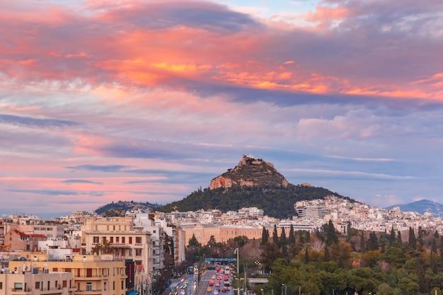 Il monte lycabettus che sovrasta i tetti della città vecchia al meraviglioso tramonto ad atene, grecia