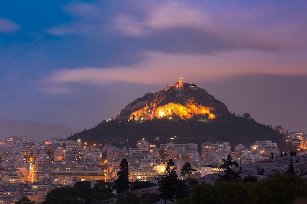 Il monte lycabettus che sovrasta i tetti della città vecchia al tramonto ad atene, grecia