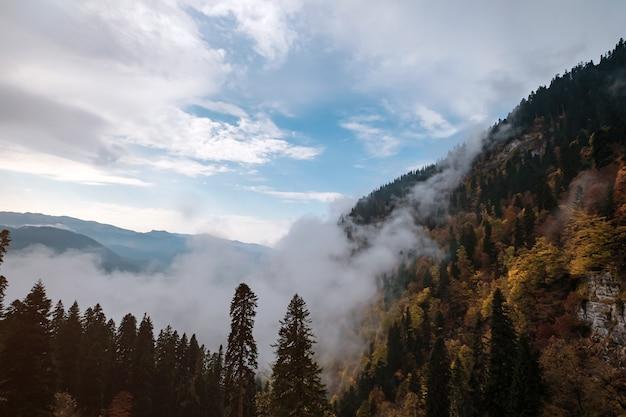Il paesaggio autunnale di montagna con foreste colorate e alte vette delle montagne del caucaso. stazione sciistica di rosa khutor in bassa stagione, russia, sochi. danza delle nuvole di montagna