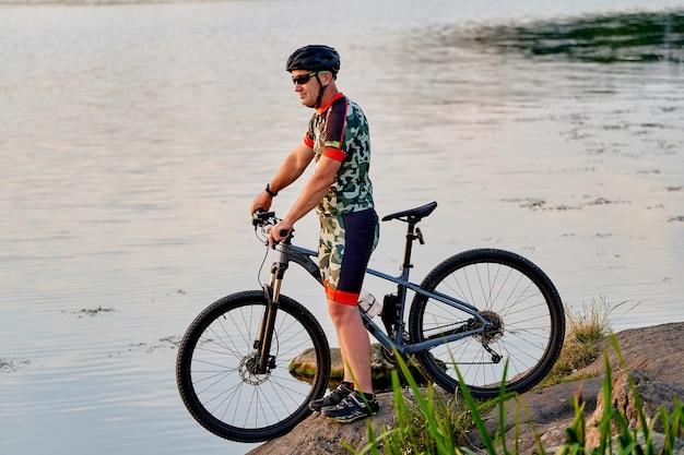 Mountain bike guardando vista e viaggiando in bicicletta. paesaggio lacustre.