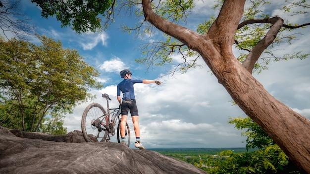 Supporto per mountain bike con coppia di mountain bike mtb sulla scogliera per guardare la montagna della natura. l'atleta di mountain bike guarda la natura selvaggia in montagna. sport estremo e mtb, concetto di mountain bike downhill