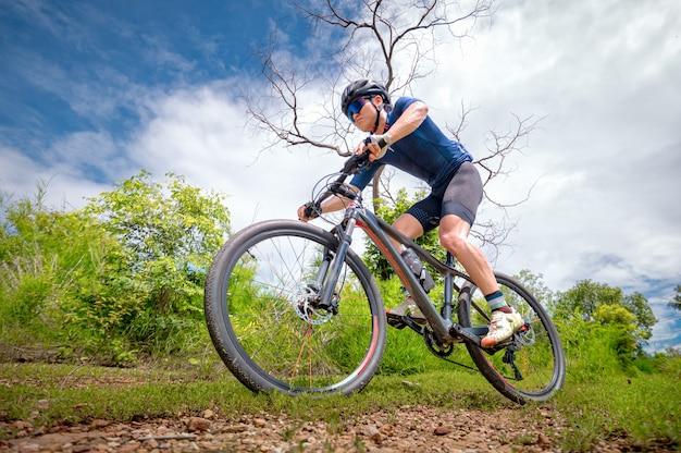 Gli appassionati di mountain bike guidano mtb, mountain bike downhill all'estremo. l'uomo asiatico guida la mtb, la mountain bike allo stato brado fino agli estremi. sport estremo e mtb, concetto di mountain bike.
