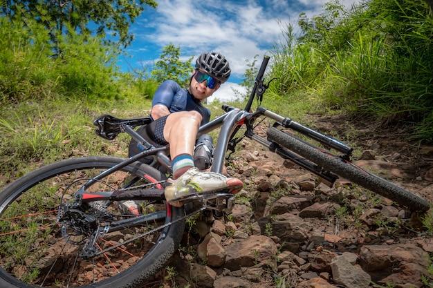 Gli appassionati di mountain bike vanno in mtb, la mountain bike in discesa ha un incidente. l'uomo asiatico guida la mtb, la mountain bike in discesa in natura ha un incidente. concetto di incidente in discesa in bici.