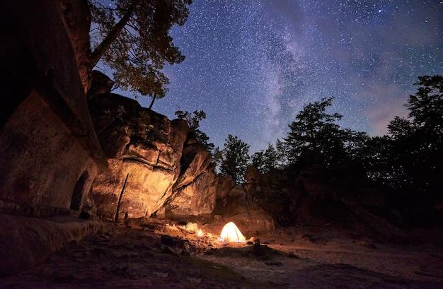 Campeggio di montagna di notte in mezzo a un'enorme formazione rocciosa ripida