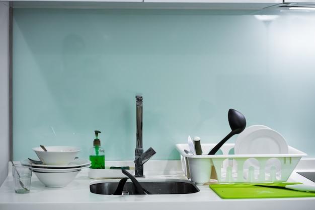 Una montagna di piatti sporchi nel lavello della cucina. pasticcio in casa
