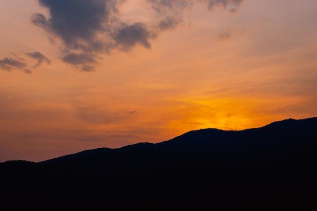 Montagna e luce dorata durante la vista del tramonto serale.