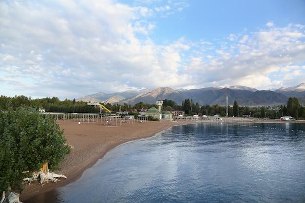 Spiaggia del lago di montagna con nuvole nel cielo blu