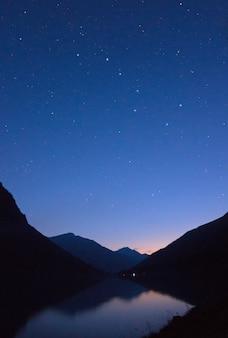 Lago di montagna in montagna sullo sfondo del cielo notturno stellato