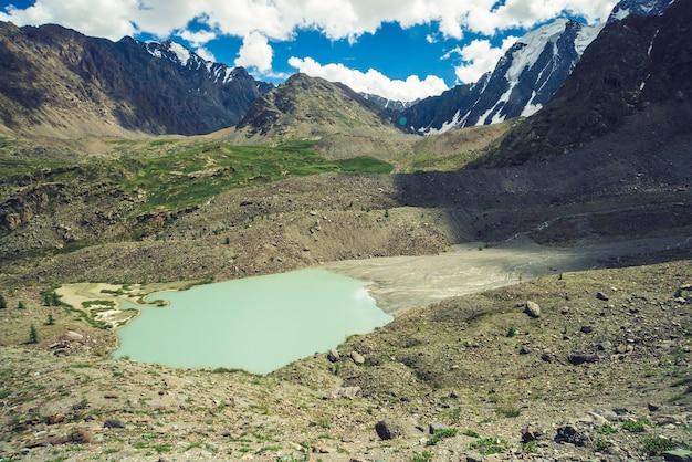 Lago di montagna a forma di cometa vicino a enormi montagne rocciose. incredibili creste montuose innevate. ghiacciaio gigante meraviglioso sotto cielo blu nuvoloso. atmosferico paesaggio cosmico di natura maestosa degli altopiani.