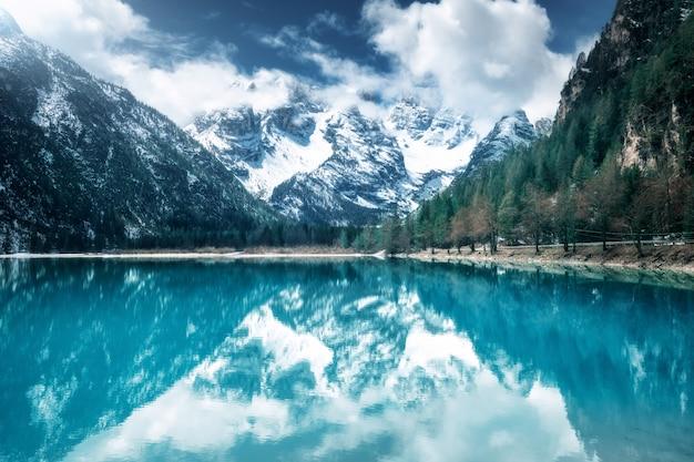 Lago mountain con la riflessione perfetta al giorno soleggiato in autunno. dolomiti, italia. bellissimo paesaggio con acqua azzurrata, alberi, montagne innevate in nuvole, cielo blu in autunno.
