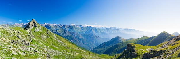 Paesaggio montano sulle alpi, montagne rocciose in alta quota, lunatico cielo verde valle e sentieri per vacanze estive turistiche