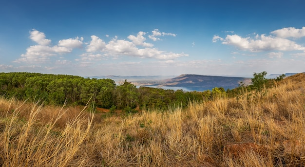 Paesaggio di montagna con fiume sul cielo blu