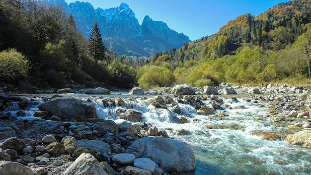 Paesaggio di montagna con torrente sulle dolomiti durante il giorno in autunno