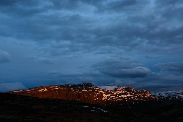 Paesaggio norvegese della montagna con il fondo di tramonto