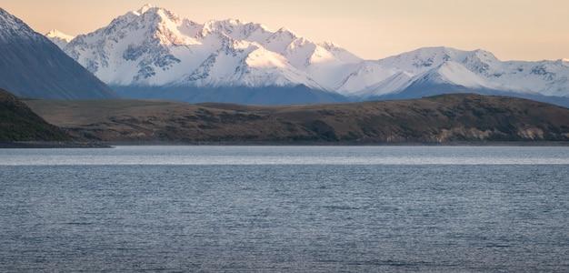 Catena montuosa durante l'alba con il lago in primo piano girato al lago tekapo, nuova zelanda