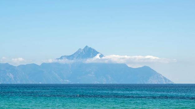 Montagna che raggiunge le nuvole in lontananza con il mar egeo in primo piano in grecia
