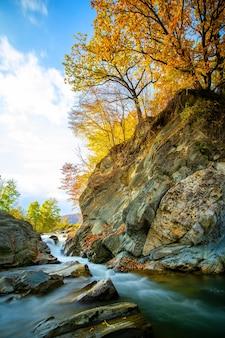 Fiume di montagna con piccola cascata con acque turchesi chiare che cadono tra massi bagnati con spessa schiuma bianca il giorno luminoso autunnale.