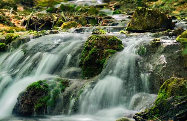 Fiume di montagna con pietre con pura acqua scongelata.