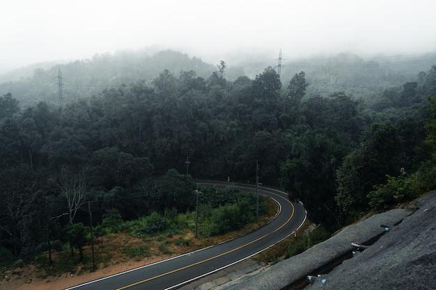 Strada di montagna in una giornata piovosa e nebbiosa, strada per pai