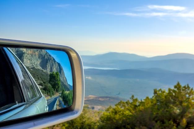 Strada di montagna in una giornata di sole estivo. vista panoramica dall'alto e specchietto retrovisore auto