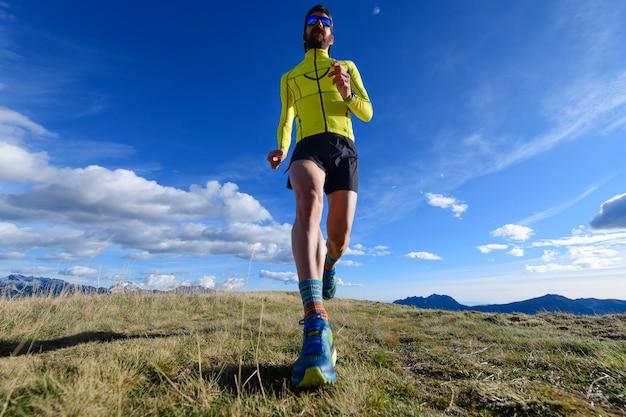 Il corridore di montagna in un prato si allena per una maratona