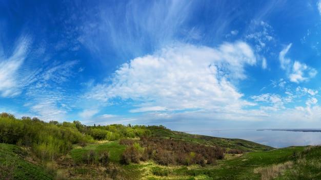 Riva del mare della montagna nella caduta contro il cielo blu con le nuvole.