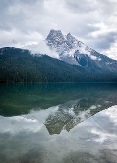 Montagna avvolta da nuvole riflesse nelle acque ferme del lago verdastro