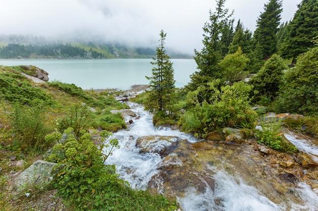 Il ruscello di montagna sfocia nel grande bacino idrico del grande lago di almaty di acqua potabile fresca