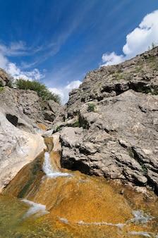 Ruscello di montagna scorre sulle rocce attraverso le pietre. le rocce hanno cambiato colore a causa del contatto con l'acqua