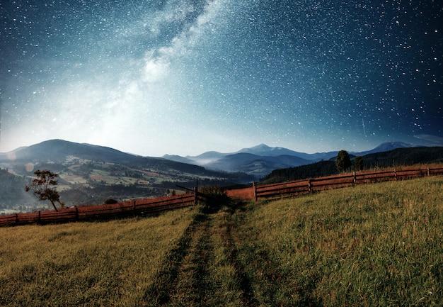 Paesaggio estivo di montagna. erba alta e cielo notturno vibrante con stelle e nebulosa e galassia. astrofotografia del cielo profondo