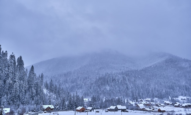 Villaggio di montagna al mattino. sta nevicando in montagna in una valle al paesaggio di montagne