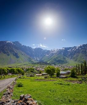 Paesaggio estivo panoramico del villaggio di montagna con prato verde e picco innevato di montagna contro