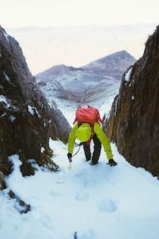 Alpinista che scala una montagna di neve