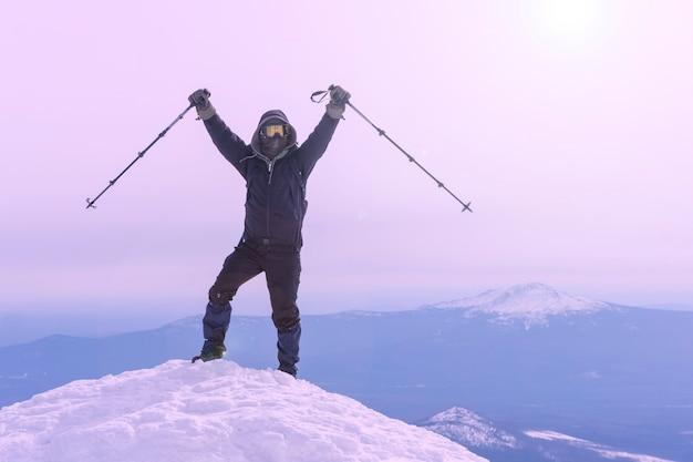 L'alpinista esulta raggiungendo la vetta della montagna