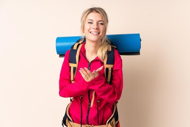 Donna alpinista con un grande zaino sopra la parete isolata che applaude