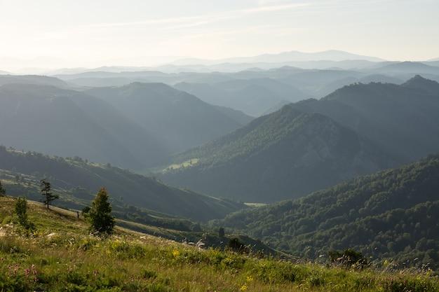 Un paesaggio nebbioso montuoso nei raggi del sole all'alba. in lontananza, si possono vedere molti strati di montagne.