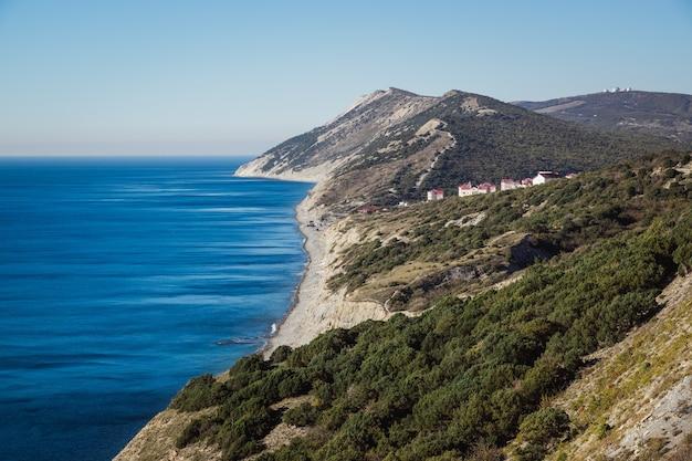 Spiaggia rocciosa montuosa coperta di foresta di ginepro in estate.