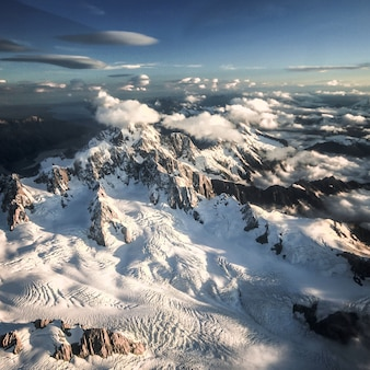 Montagne coperte di neve e avvolte da nuvole ripresa aerea franz josef nuova zelanda