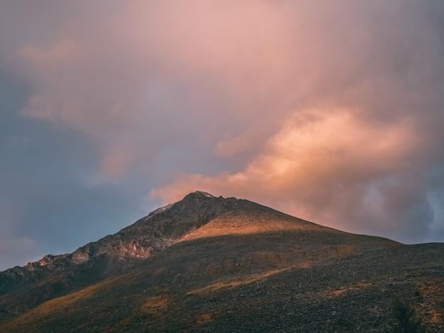 Montagne all'alba. paesaggio atmosferico con sagome di montagne sullo sfondo del cielo rosa dell'alba. paesaggi naturali colorati con tramonto o alba. tramonto in toni sbiaditi.