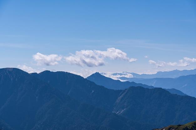 Montagne e colline panoramia vista con molte catene nebbiose e fumose accatastate.
