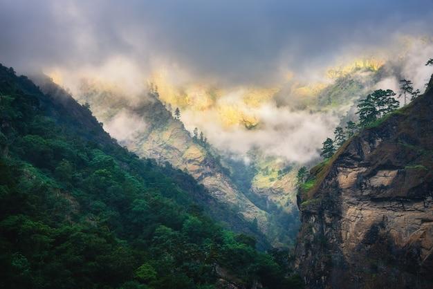 Montagne in nuvole basse in serata nuvolosa in nepal. paesaggio lunatico con bellissime rocce alte e cielo nuvoloso drammatico, luce solare, foresta verde nella nebbia al tramonto. sfondo della natura. montagne himalayane