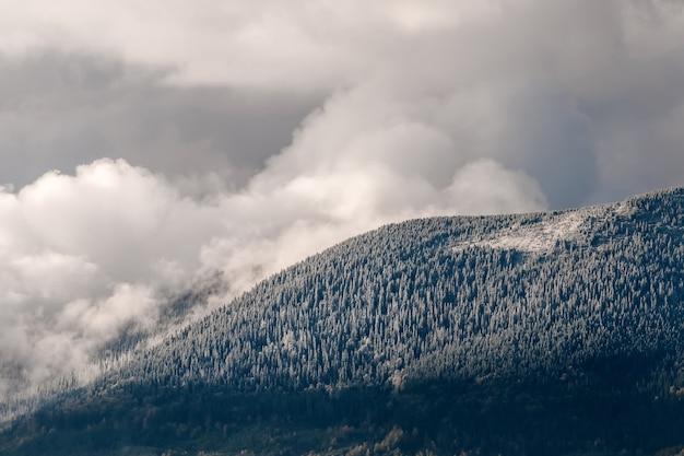 Le montagne innevate su uno sfondo di nuvole maestose