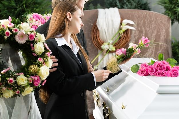 Lutto uomo e donna al funerale con rosa rosa in piedi alla bara o bara