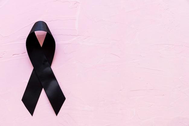 Nastro di lutto e melanoma nero su sfondo rosa